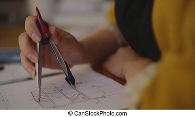 Close-up Young female architect working on blueprint using the compass and enter the data into an electronic tablet
