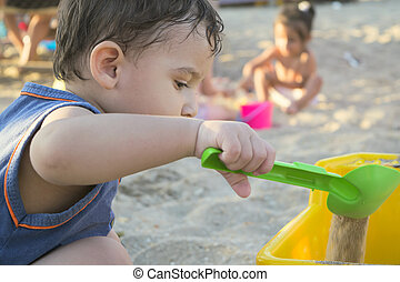 boy on the beach playing with sand