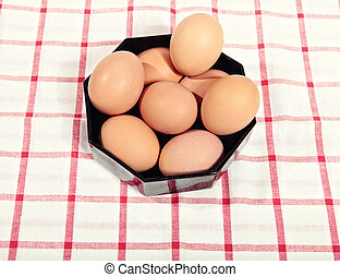 Chicken eggs in a black bowl on cloth in red cell