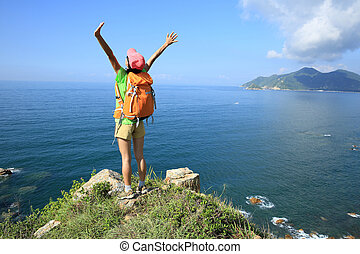 cheering young woman hiker open arms on seaside mountain...