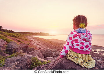 Adorable little girl looking at the sunset Northumberland...