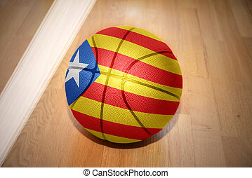 basketball ball with the national flag of catalonia lying on...