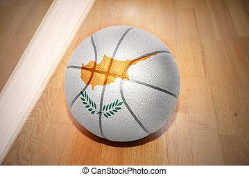 basketball ball with the national flag of cyprus lying on...