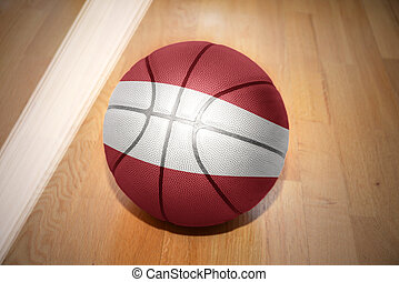 basketball ball with the national flag of latvia lying on...