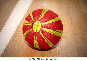 basketball ball with the national flag of macedonia lying on...