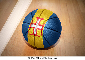basketball ball with the national flag of madeira lying on...