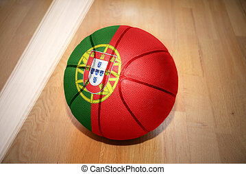 basketball ball with the national flag of portugal lying on...