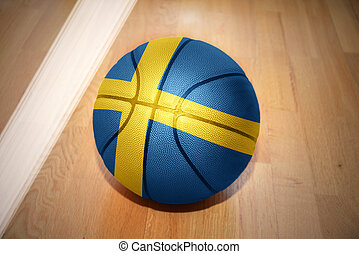 basketball ball with the national flag of sweden lying on...