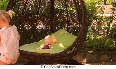 little blonde girl with hairtails rocks doll on round swing