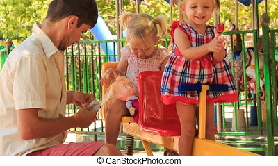 father feeds little girls on double swing in tropical park