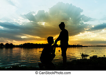 Silhouette of couple beside the river with beautiful sunset