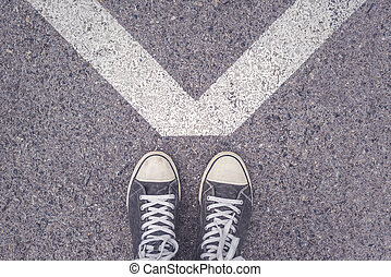 Standing above V shaped sign on urban pavement - Man...