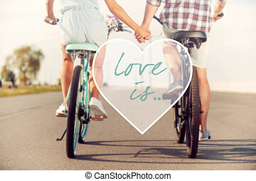 Love is Rear view of young couple holding hands while riding...