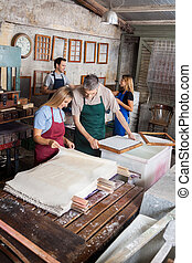 Workers Looking At Drying Papers In Factory
