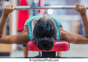 Woman workout with barbell on the bench - Young woman...