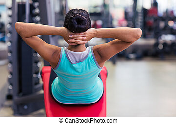 Woman workout on exercises machine - Back view portrait of a...