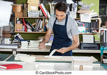 Worker Working At Table In Paper Industry - Mid adult male...