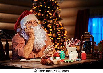 Pensive Santa Claus with Christmas deer and paintbrush
