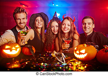 Toasting dreadful Halloween - Young people cheering at...