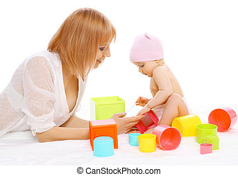 Mother and baby playing together with colorful toys