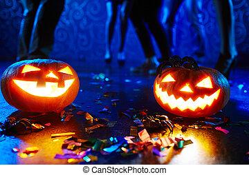 Halloween night - Pumpkin lanterns on floor among confetti