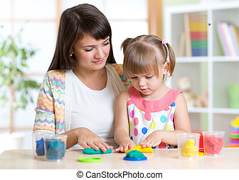 Young woman and kid playing with colorful clay molding...