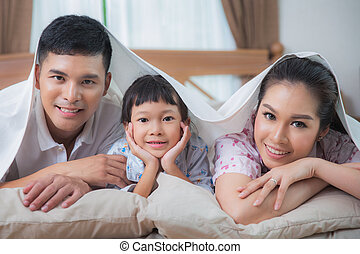 Family in the duvet smiling on the bed - Asian Family in the...
