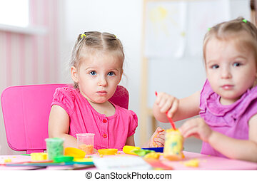 Kids playing with colorful clay molding different shapes -...