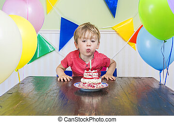 Boy blowing out a birthday candle - Cute kid blowing out a...