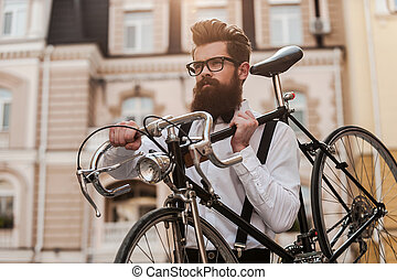 Bearded man with retro bicycle. Low angle view of confident...