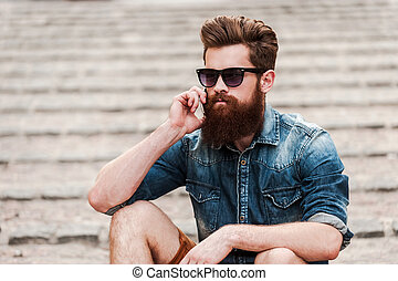 Staying in touch. Confident young bearded man talking on the...