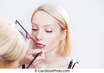 Professional Make-up artist applying makeup. - Professional...