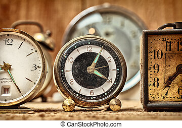 Retro styled image of old alarm clocks on a wooden table