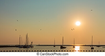 Sunset with sailing boats in Friesland