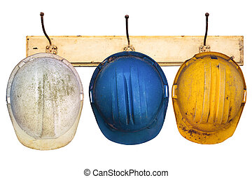 Three helmets hanging on a hat-rack - Three construction...