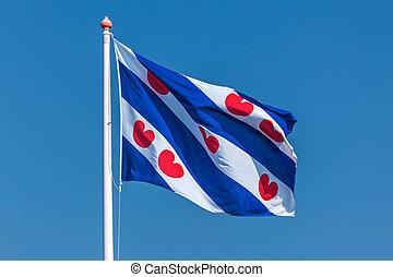 Dutch Frisian flag against a clear blue sky - Dutch flag of...