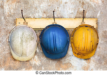Three construction helmets hanging on a hat-rack - Three...