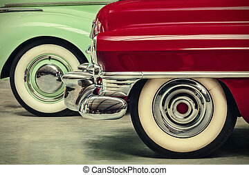 retro styled image of two vintage American cars parked next...