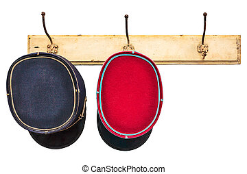 Two vintage conductor hats hanging on a hat-rack isolated on...