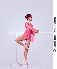 Ballerina stretching on the bar - young ballerina in a pink...