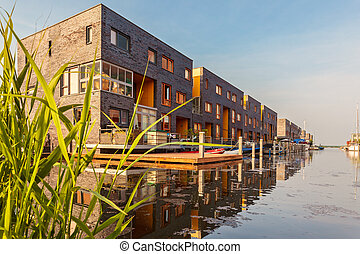 Row of Dutch modern canal houses in Almere reflected in the...