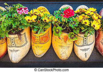 Dutch old wooden clogs with blooming flowers - Old wooden...