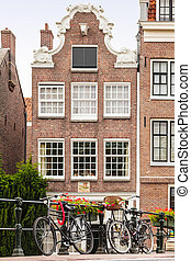 Bicycles on an Amsterdam canal bridge with an ancient canal house in the background