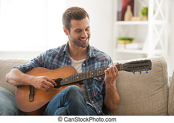 Composing his new song. Happy young man playing the guitar...
