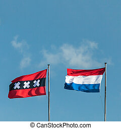The Dutch national flag and the official flag of Amsterdam -...