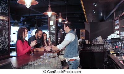 Two cute girls and a guy get his order from the bartender