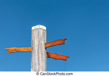 Wood carved direction signs on a beach pole