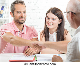 a young couple signs a contract