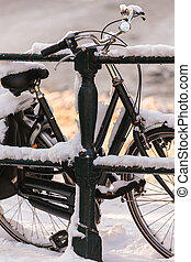 Bicycle covered with snow on a canal bridge in Amsterdam -...