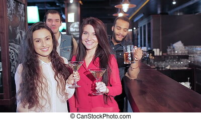Girls with martini and guys with glasses of beer at the bar greets friends